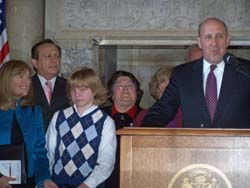 Gov. Doyle stands with an autistic boy at the Capitol.