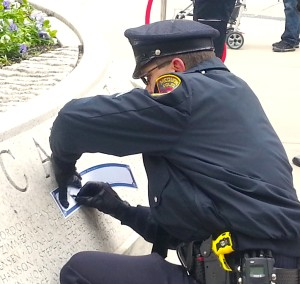 Officer etches pencil on paper to transfer name of fallen soldier to keep as memento