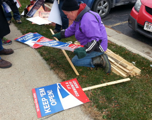 A postal worker passes out protest signs in Madison. (Photo: Andrew Beckett)