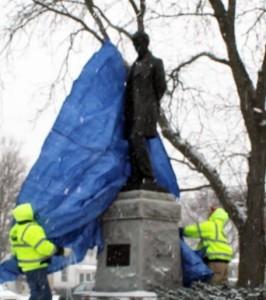 Crews remove a tarp from the restored statue. (Photo: City of Burlington)