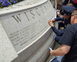 A Janesville police officer takes a rubbing of a name off Wisconsin's Law Enforcement Memorial (Photo: Andrew Beckett)