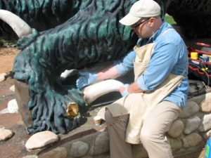 Sculptor Chuck Williams repairs the Hodag's claws. (Photo: Rhinelander Chamber of Commerce)
