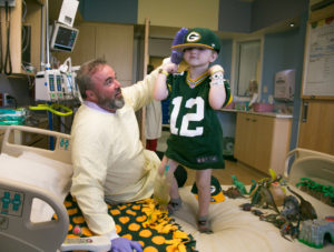 Mike McCarthy visits with a patient at American Family Children's Hospital. Photo Courtesy of John Maniali - UW Health